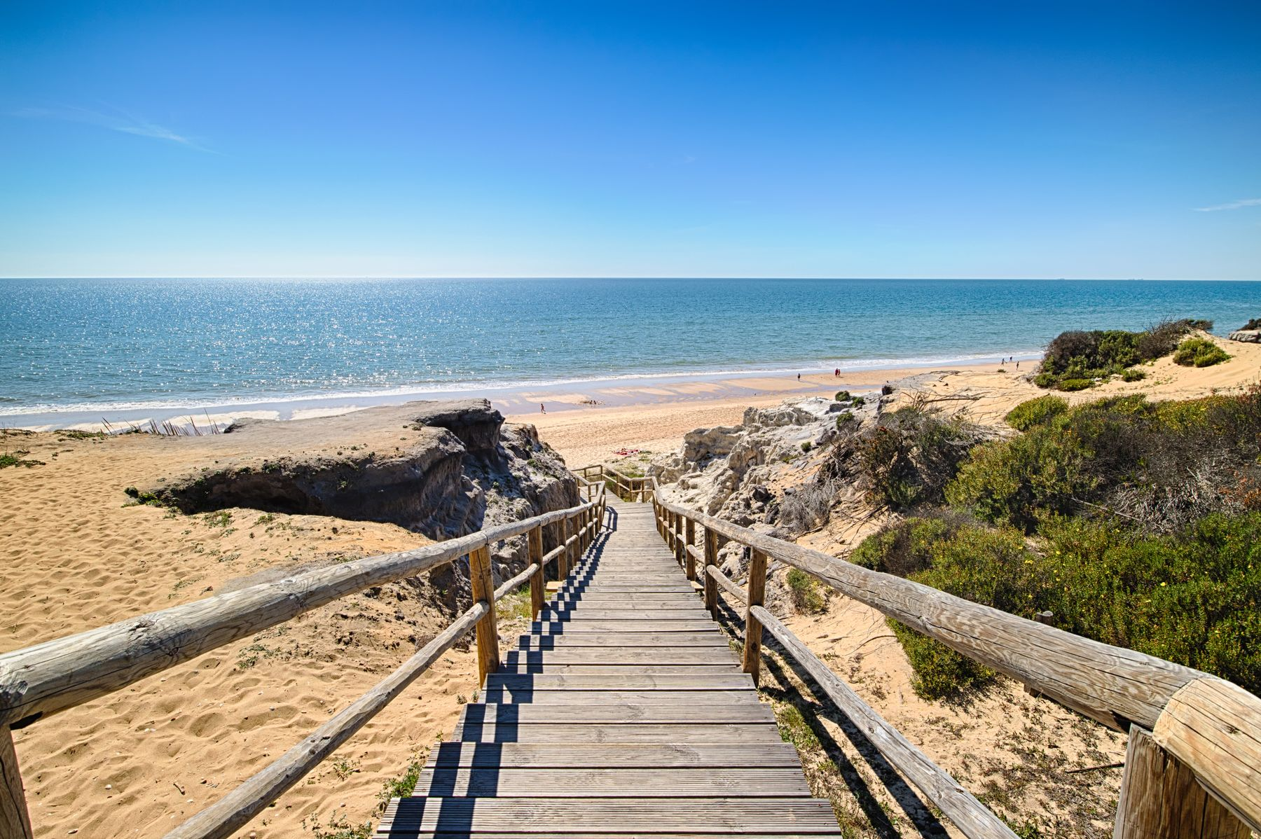 Wooden steps leading down to a quiet, sandy beach with the clear blue sky and sea in the background.