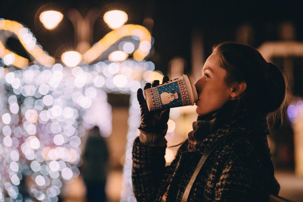 Γυναίκα πίνει ένα ζεστο ρόφημα σε χριστουγεννιάτικη αγορά.