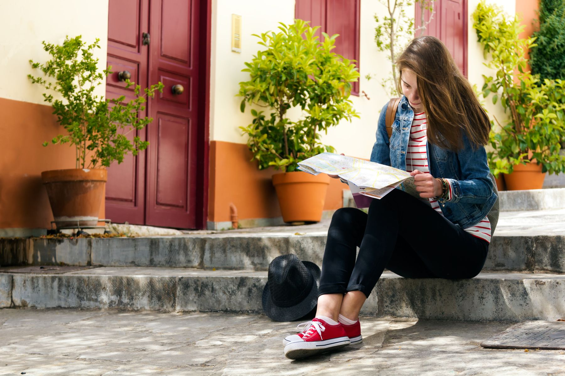 girl sitting on steps looking at map planning travel