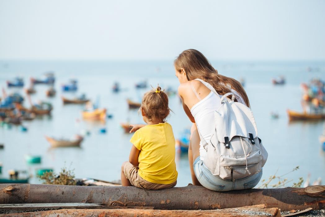 Μητέρα με βρέφος κοιτάζουν τις βάρκες στη θάλασσα - tips για φθηνές διακοπές με παιδιά
