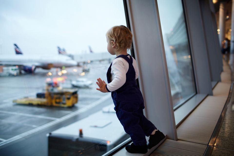 Μικρό παιδί κοιτάζει τα αεροπλάνα μέσα από το τζάμι του τερματικού σταθμού αεροδρομίου