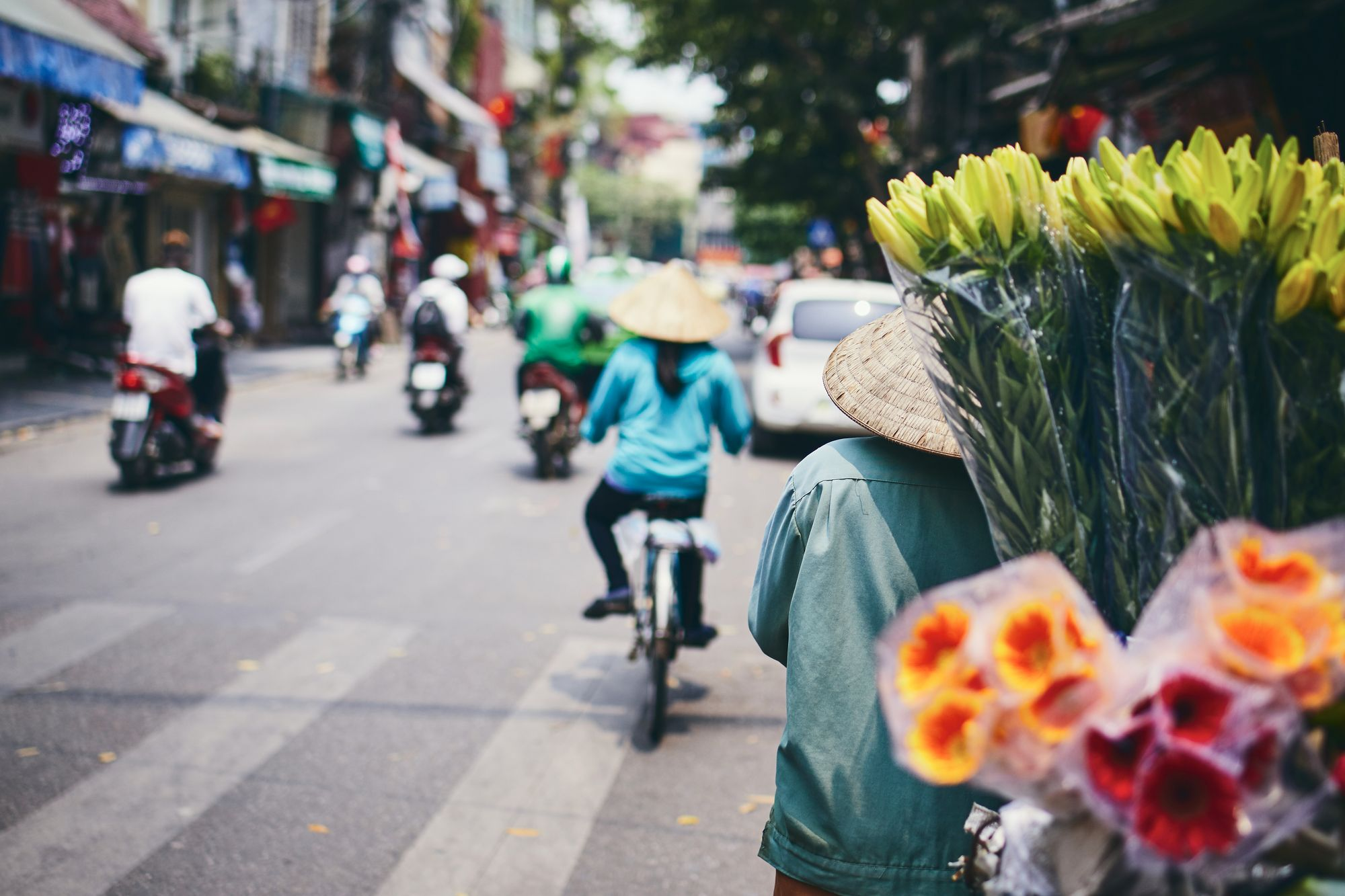 City life in street of old quarter in Hanoi. Flower vendor in traditional  conical hat.