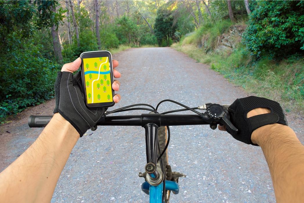 Άντρας σε ποδήλατο τσεκάρει διαδρομές για mountain bike στο κινητό του