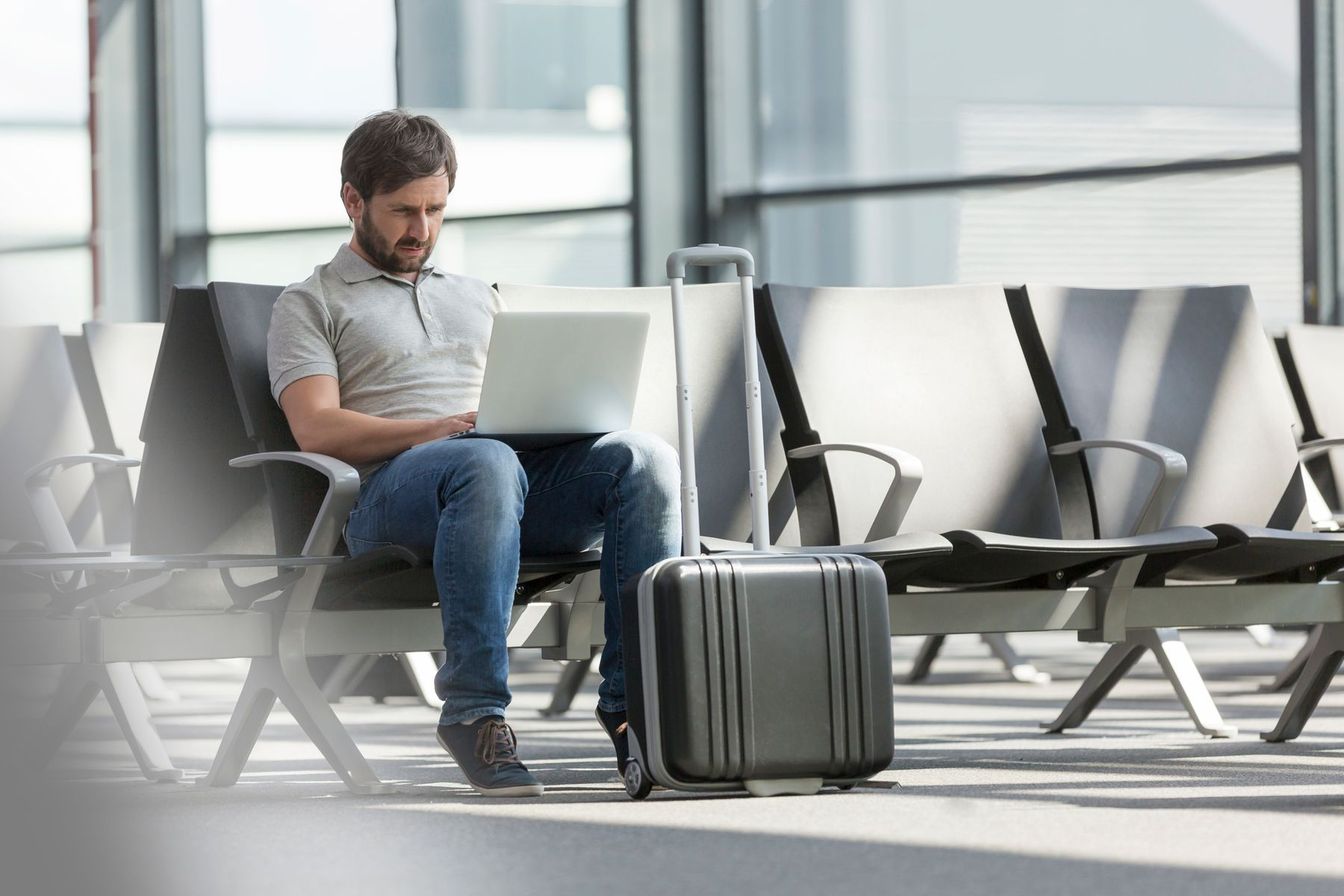Man using laptop at airport departure lounge - Flybe baggage allowances and how to beat extra charges