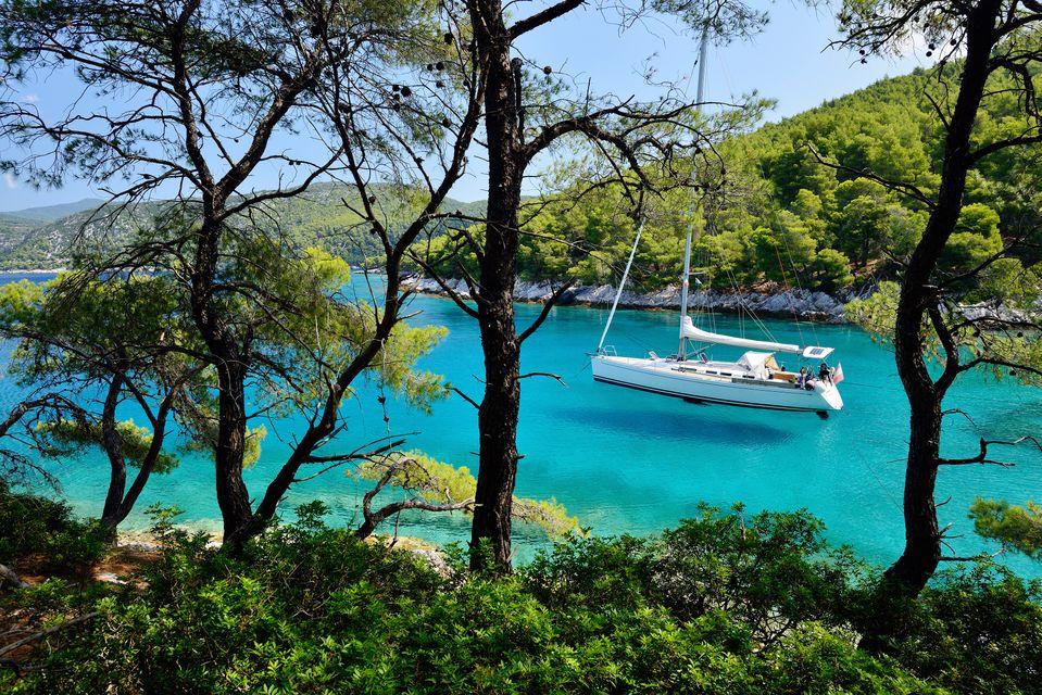 Yacht in calm turqoise waters, seen through lush green trees - Skopelos, Sporades Islands