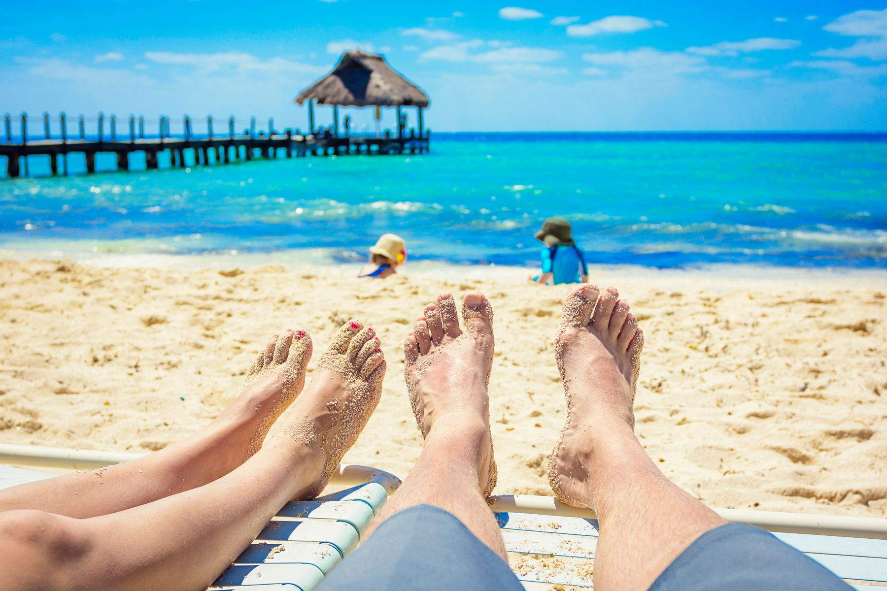 Playa del Carmen family holiday at all inclusive. Couple with their toes in the sand by the beach.