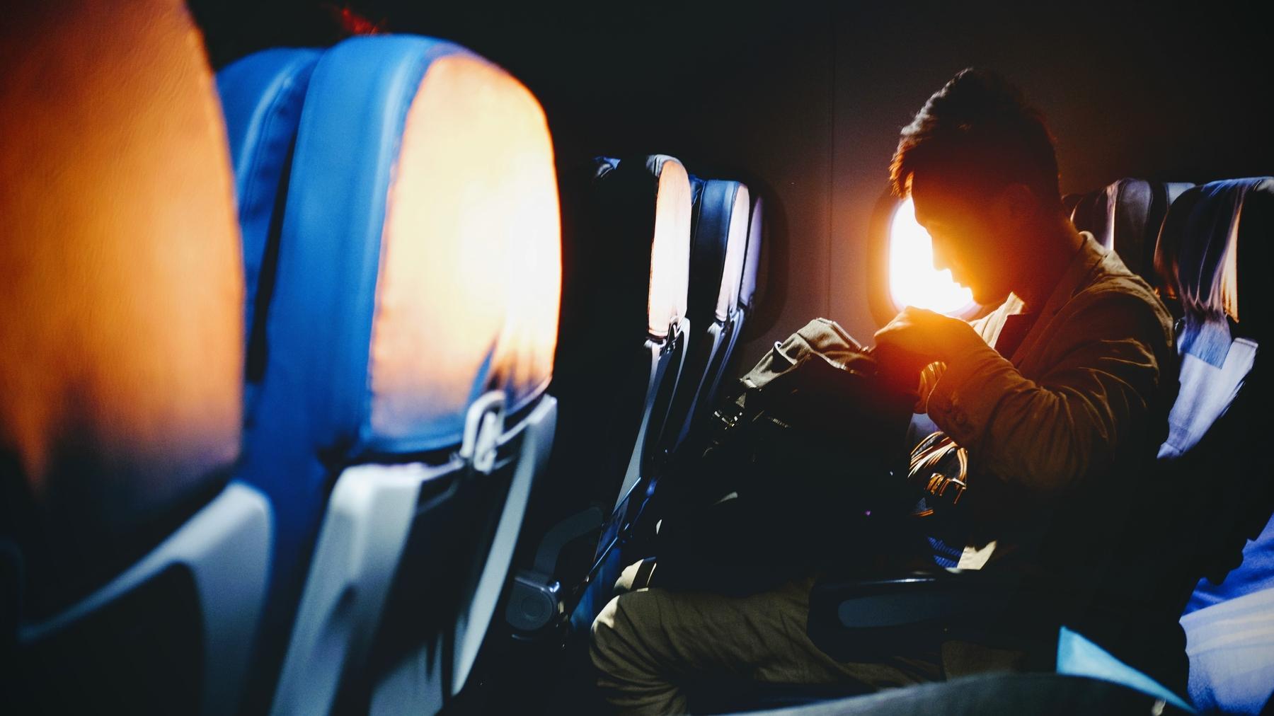 Man on board a plane checks his back