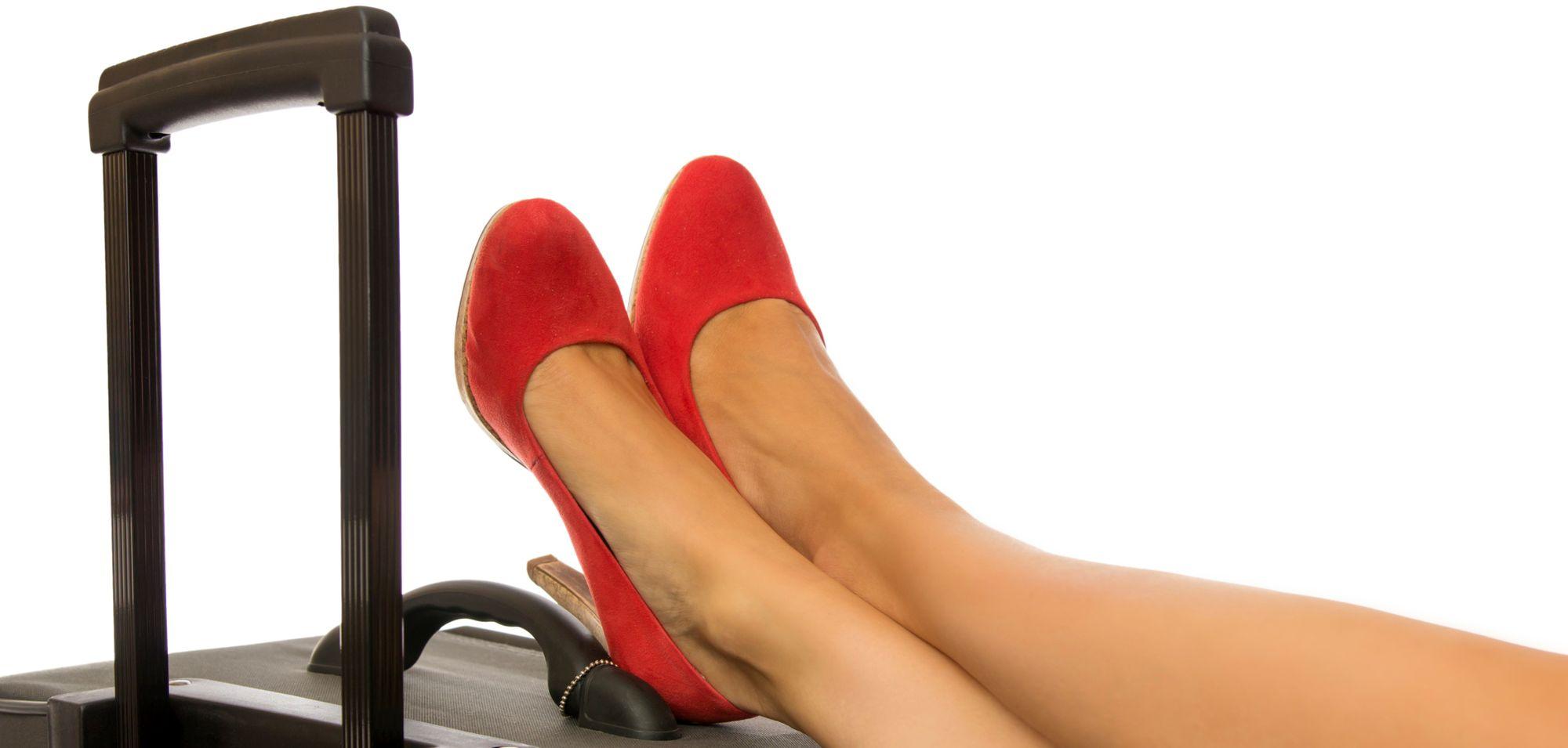 Woman with red shoes resting her feet on top of her wheelie - how to keep your luggage safe