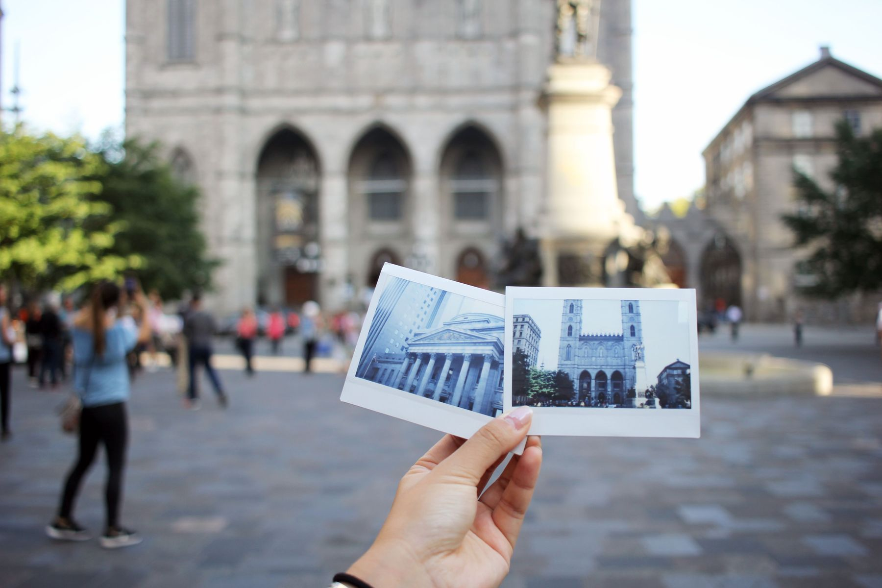 Person holding two polaroid images of Montreal architecture in front of Notre Dame Cathedral in the old port of Montreal, a great place to visit in Canada