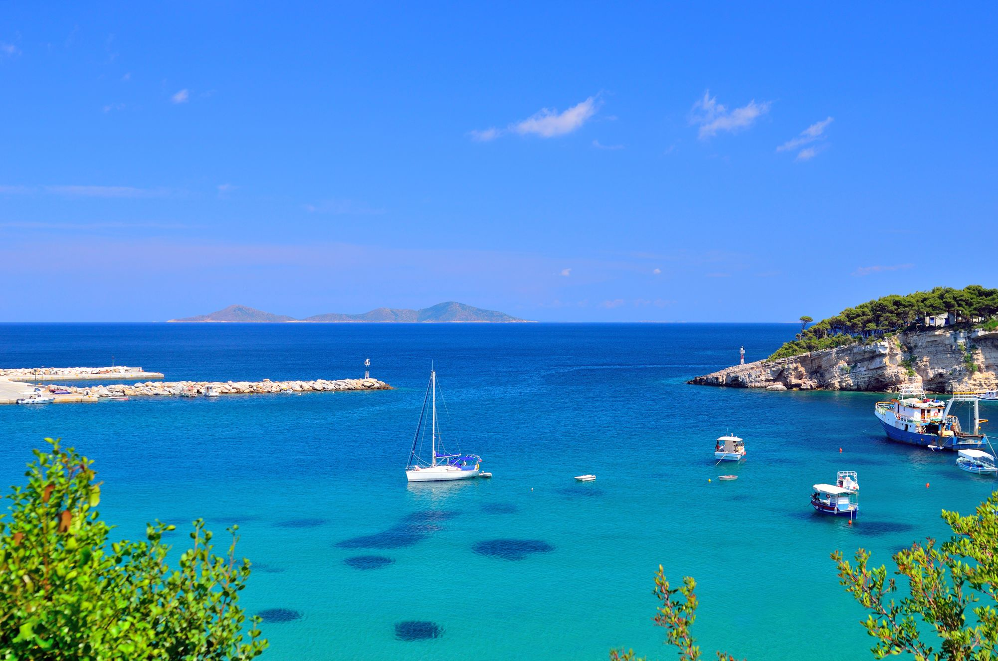 View of boats in pale blue waters in Alonissos - best Greek islands to visit in summer
