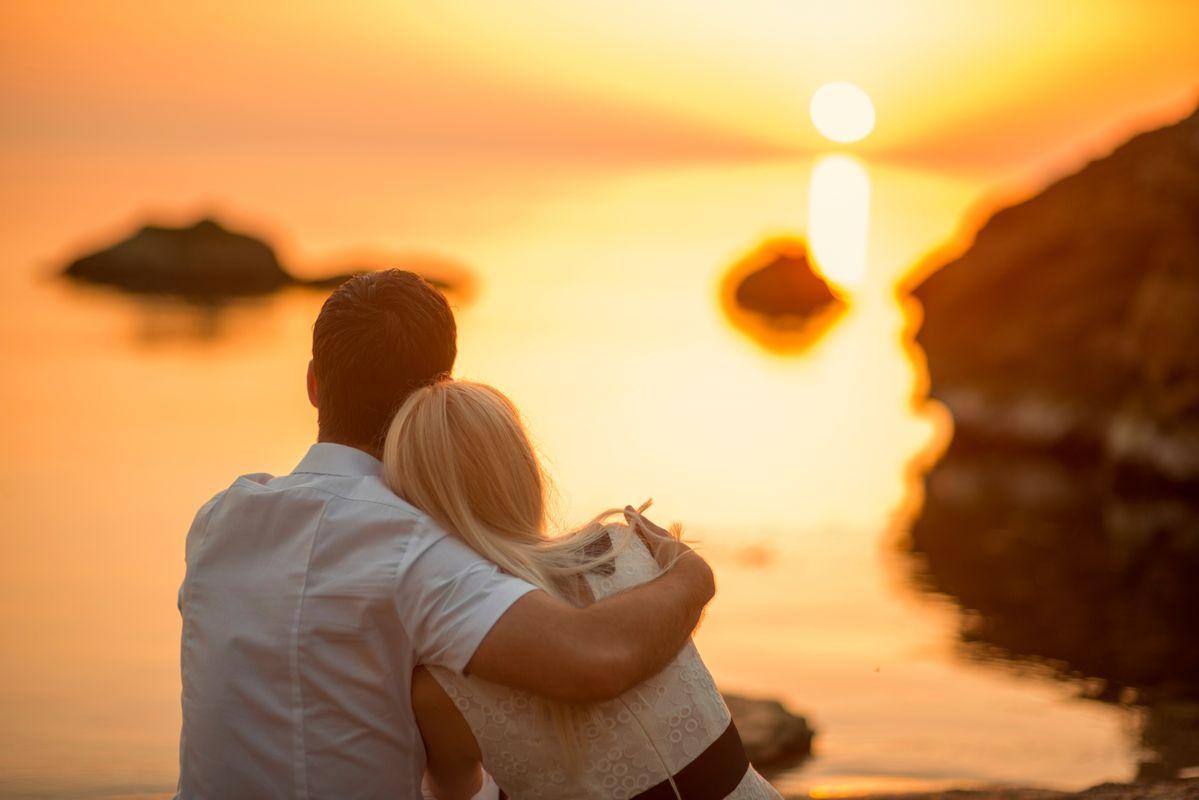 Ζευγάρι χαζεύει το ηλιοβασίλεμα στη θάλασσα