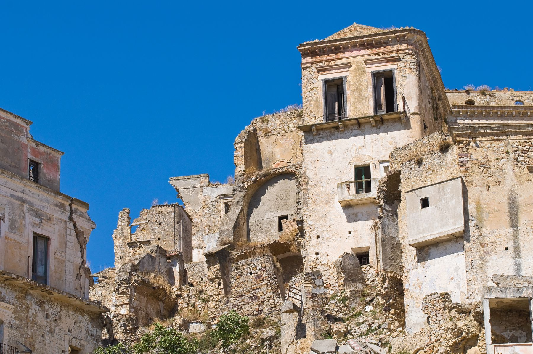 Crumbling buildings set against a blue sky in Craco, Italy.