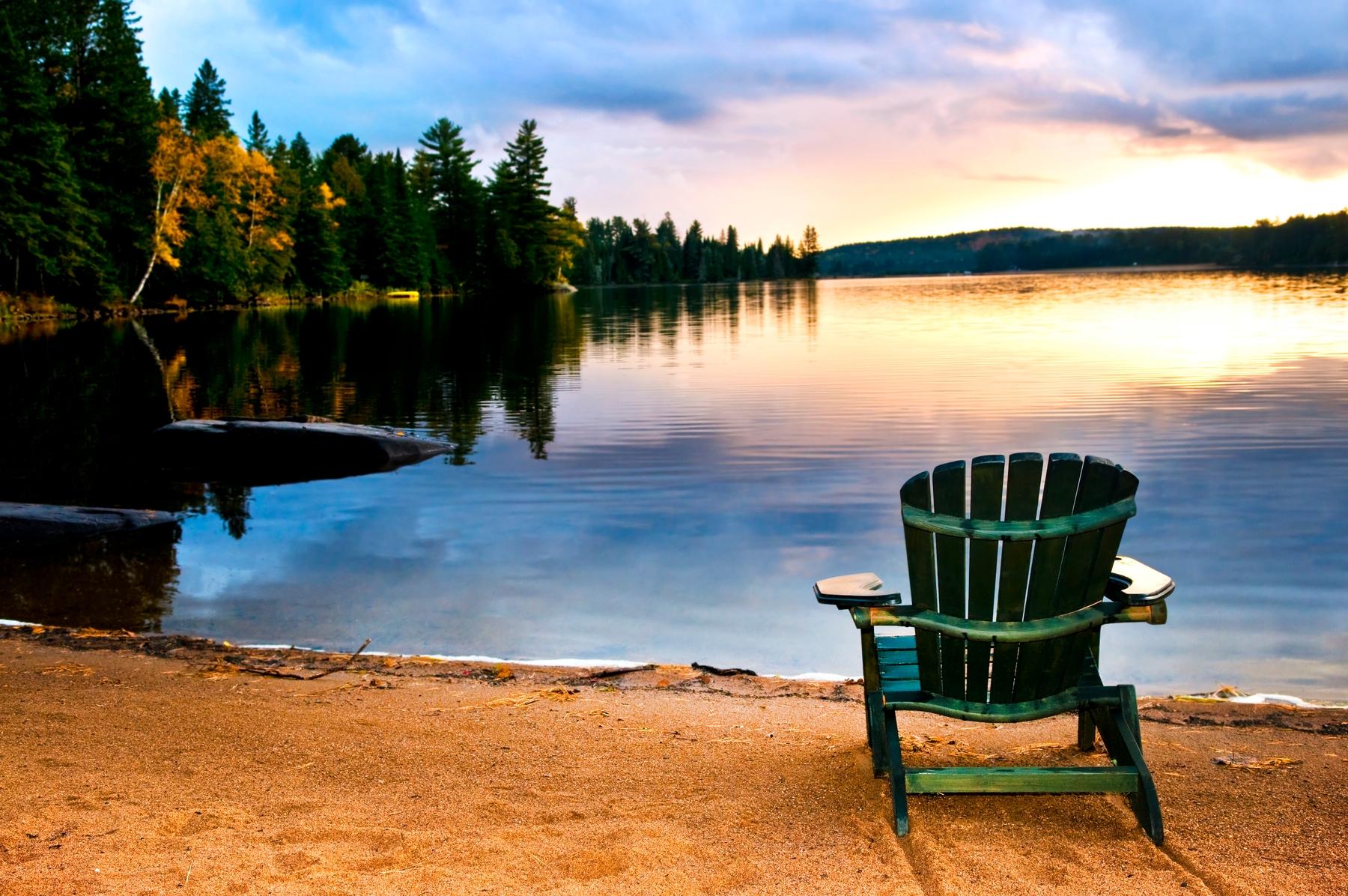 Muskoka chair by the lake at sunset