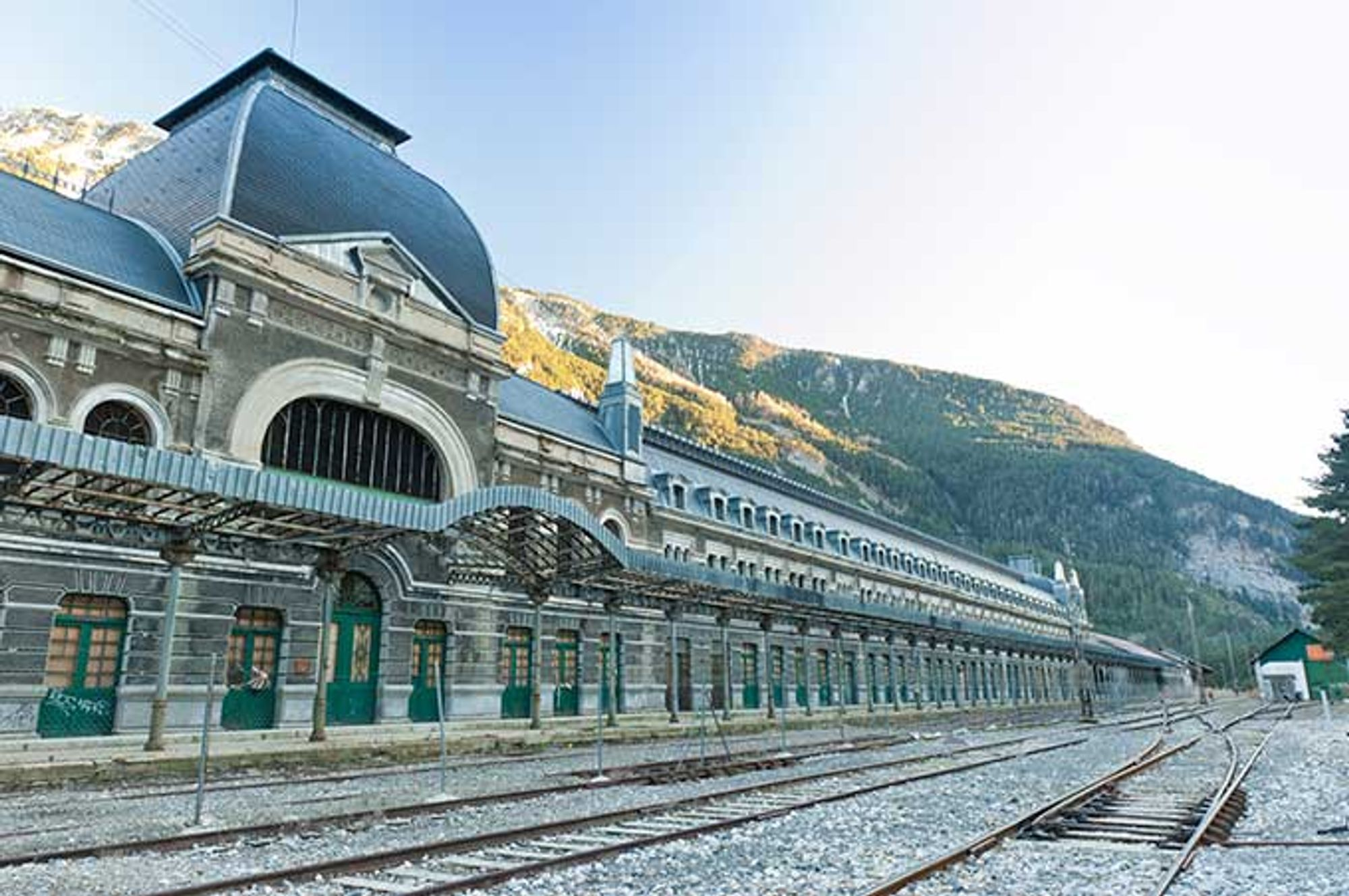 The elegant Canfranc train station, with mountains in the background as empty train tracks roll in front.