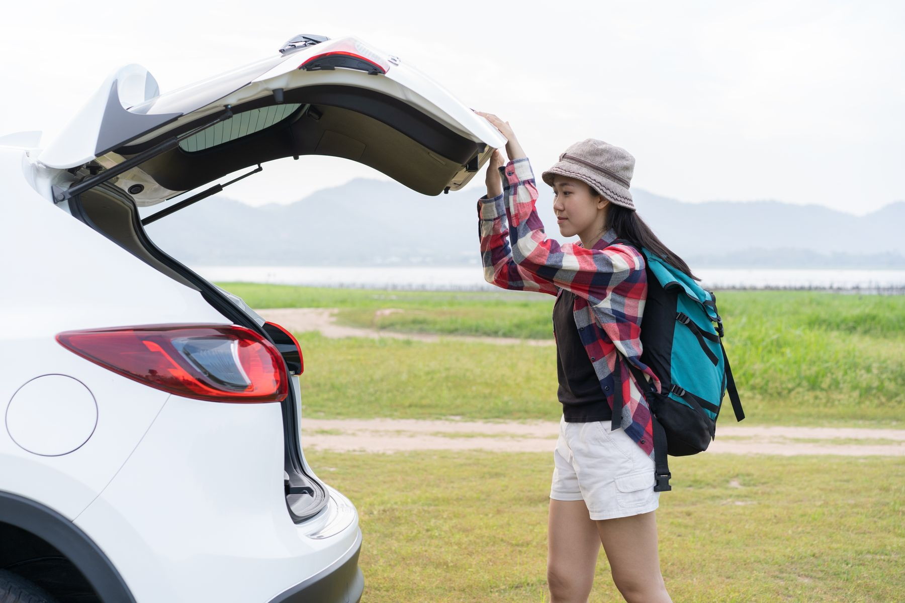 A woman closing the trunk of a car