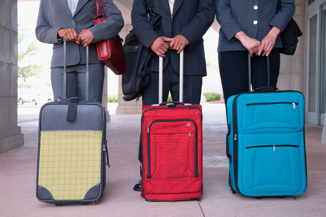 Three people holding wheelie suitcases for cabin baggage