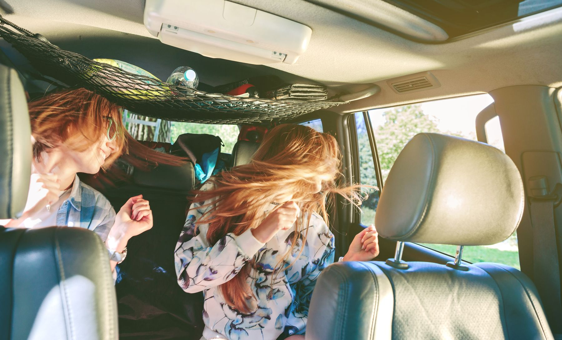 two girls dancing in a car during road trip