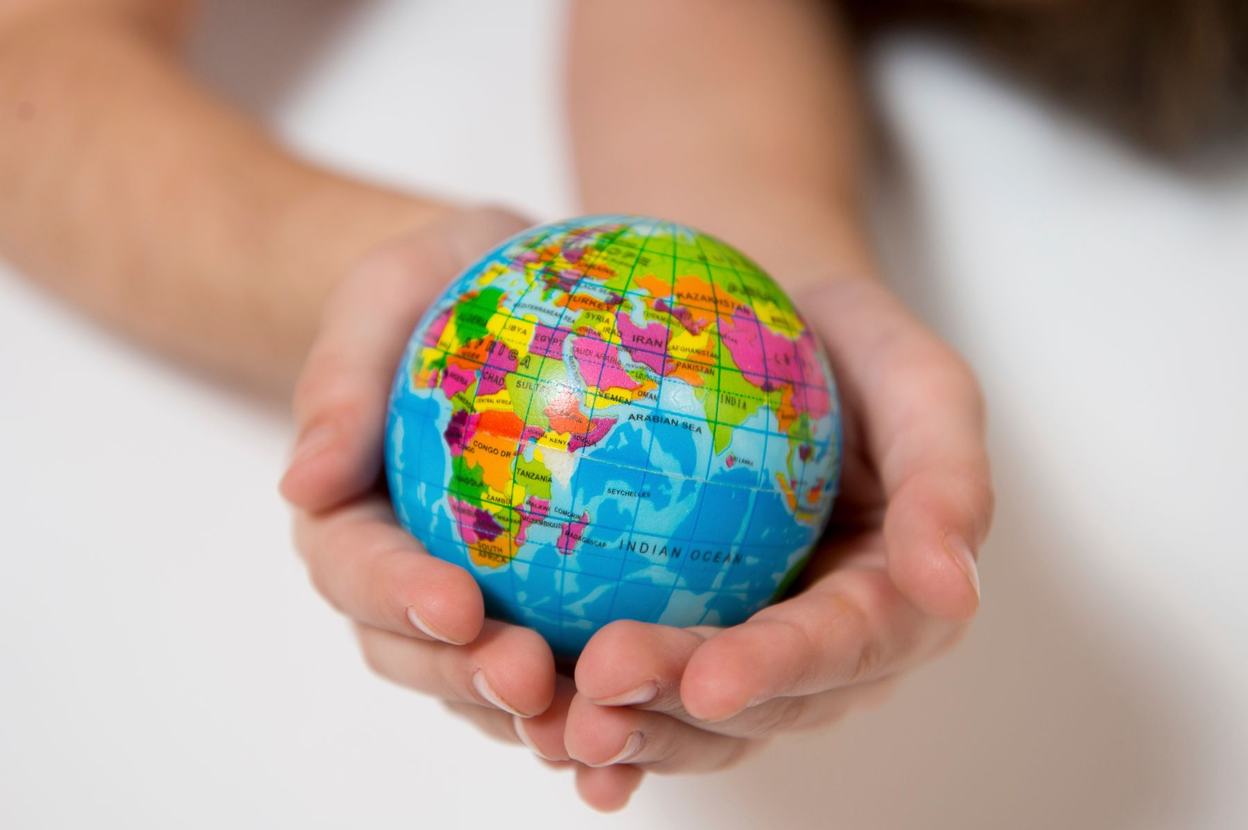 Person holding small globe in hands
