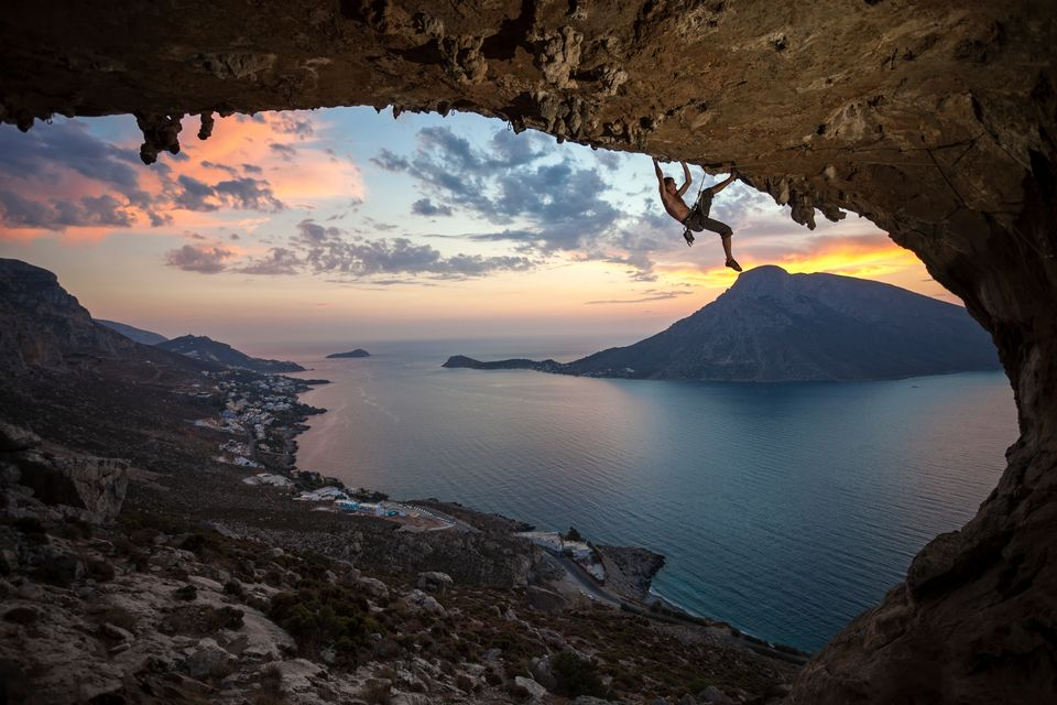 Climber on top of Grande Grotta Cave in Kalymnos - what to eat and do in Greek islands