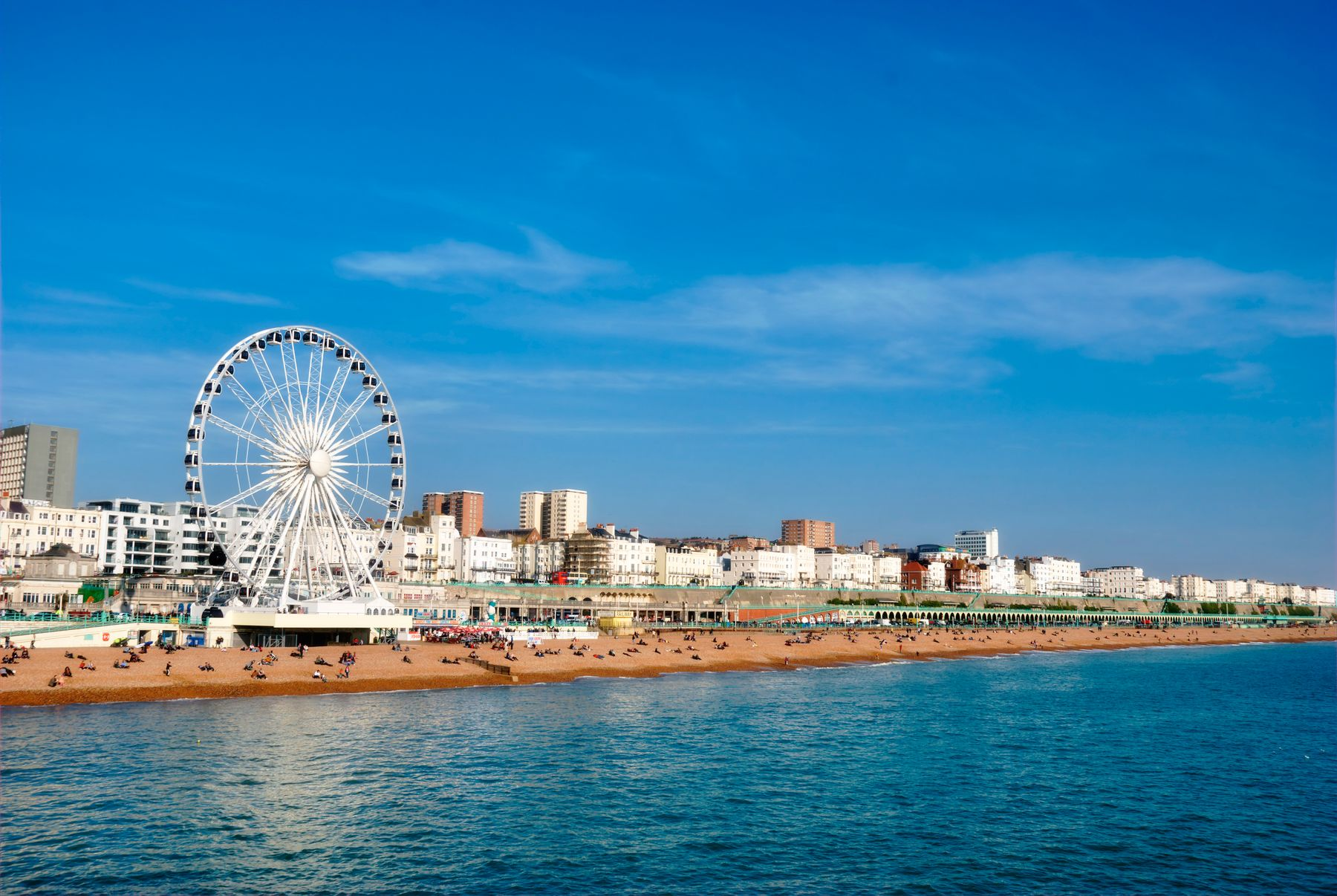 Picture shows Brighton, one of the best cities to visit in the UK, with Brighton seafront with its sandy beach, and the Brighton Wheel - the weather is sunny and the sky is blue.