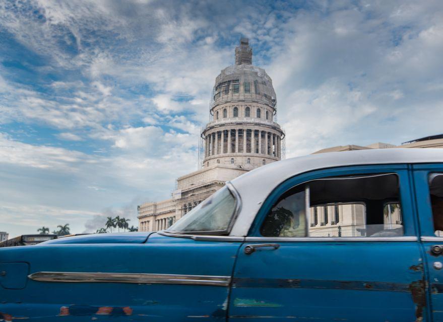 Синий ретроавтомобиль на фоне Капитолия в Гаване.