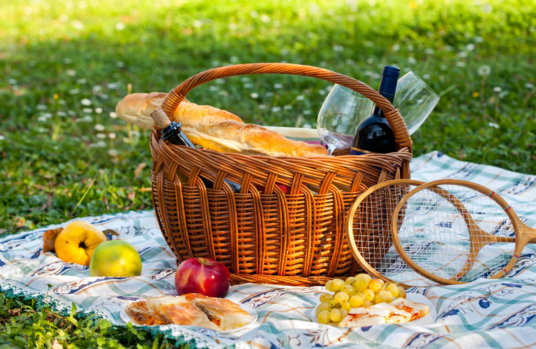 a picnic basket with baguette and wine in a park