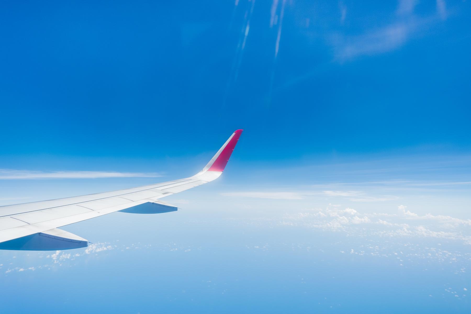 Asa de avião com azul do céu e nuvens ao fundo