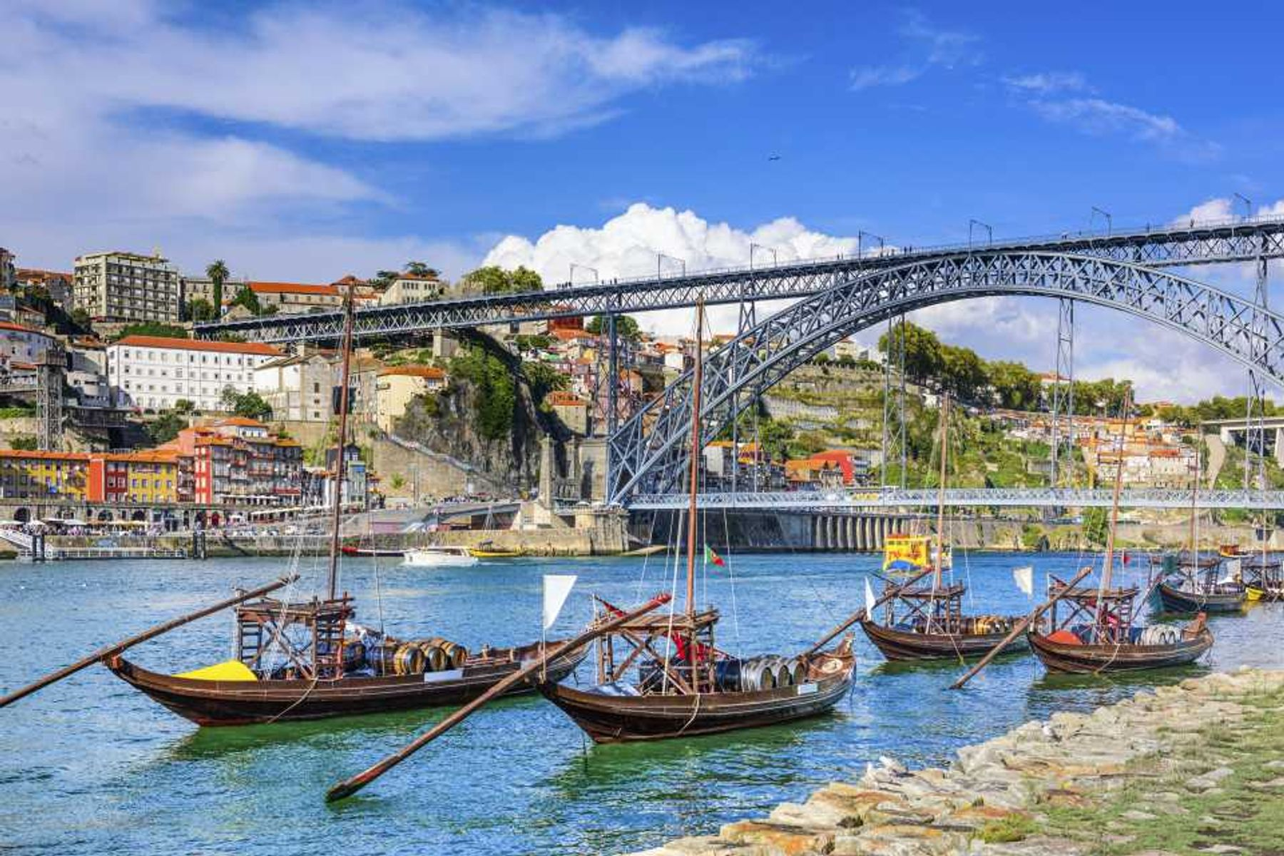 View of Porto from Vila Nova de Gaia with Dom Luis I bridge in the background and old-fashioned boats in the foreground