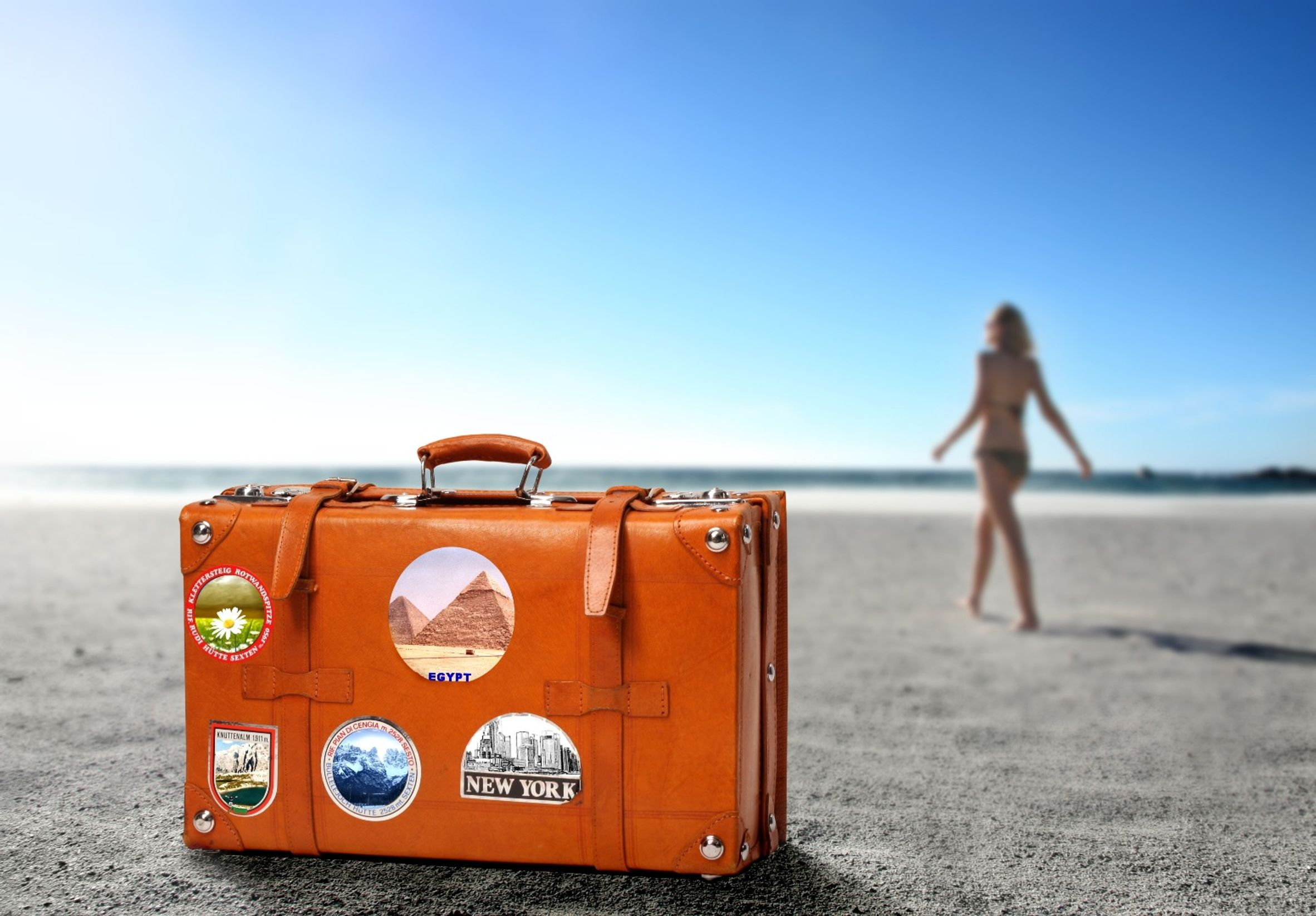 Suitcase with stickers on is sitting on a beach, as a girl is walking towards the sea
