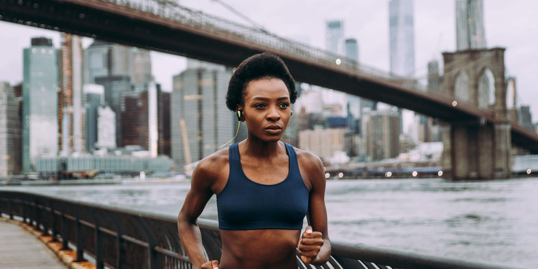 Person running next to a river with New York skyline behind them