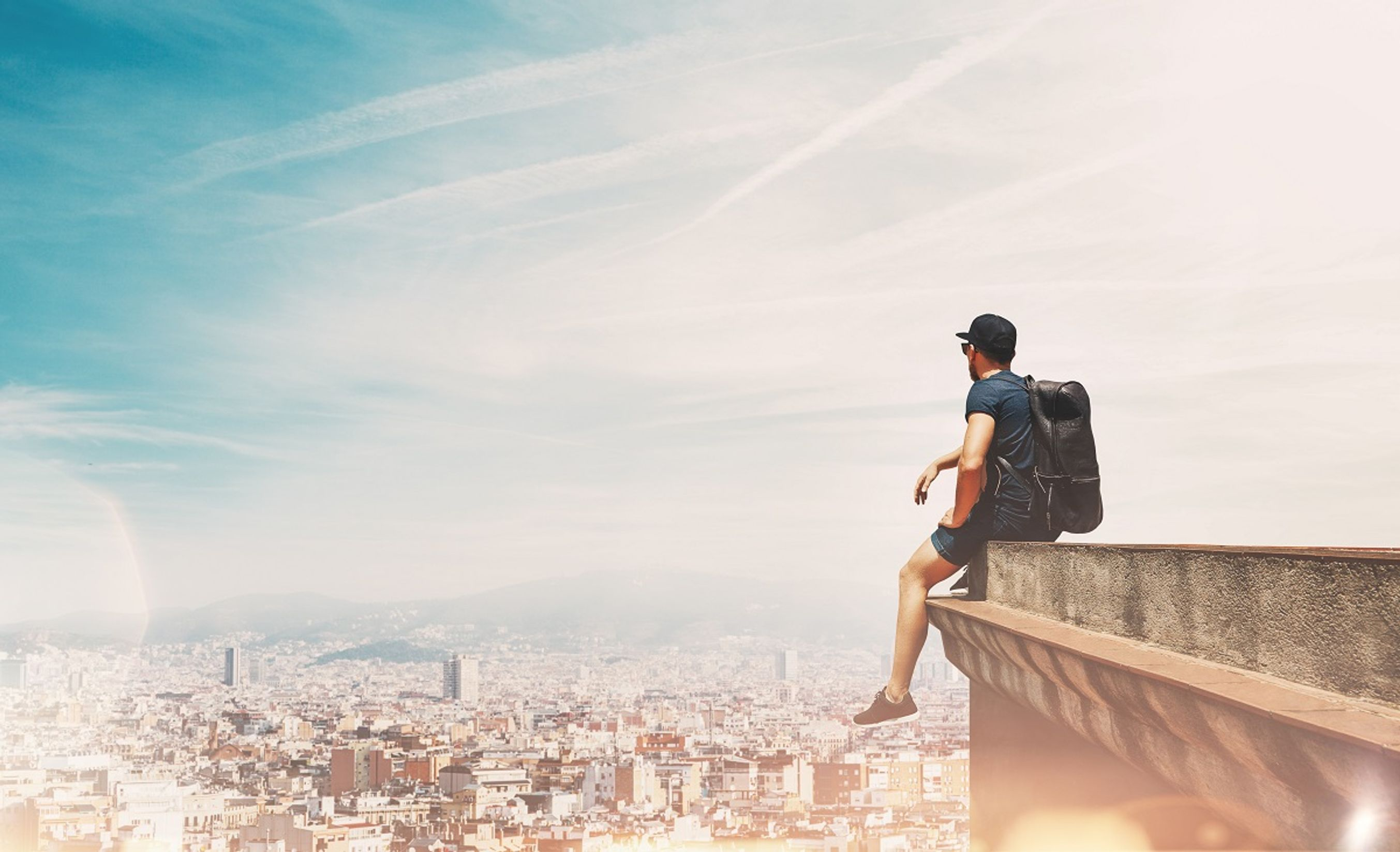 Man on a roof watching the sunset in Barcelona - 5 best weekend breaks for studens