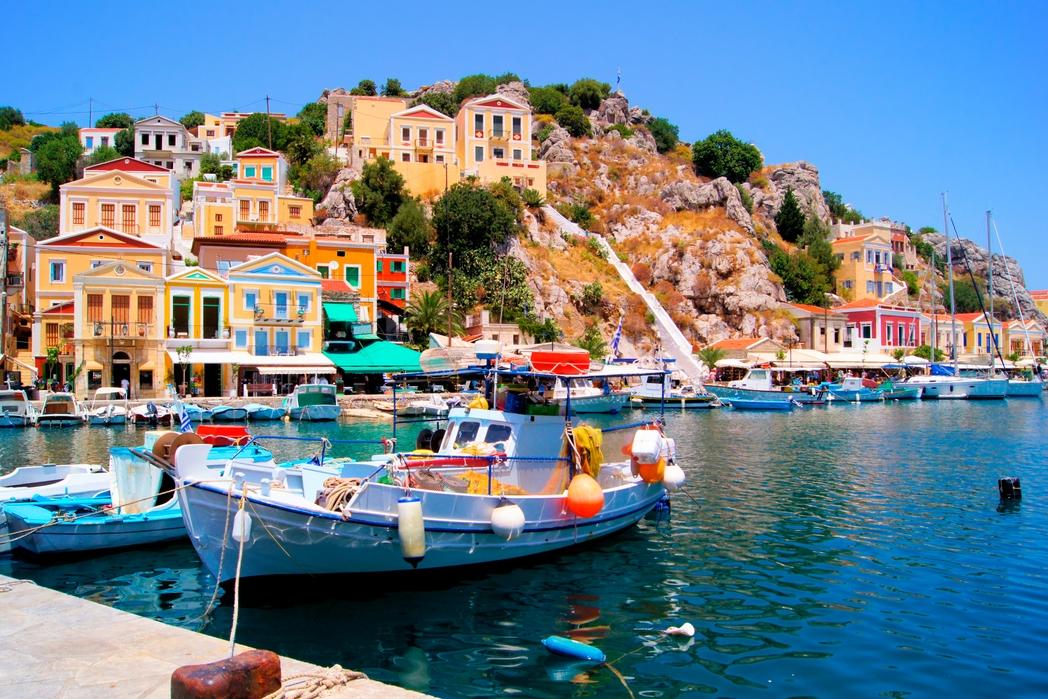 Το πολύχρωμο λιμάνι της Σύμης, ψαρόβαρκες και κτίσματα σε κίτρινους, κόκκινους και γαλανούς χρωματισμούς