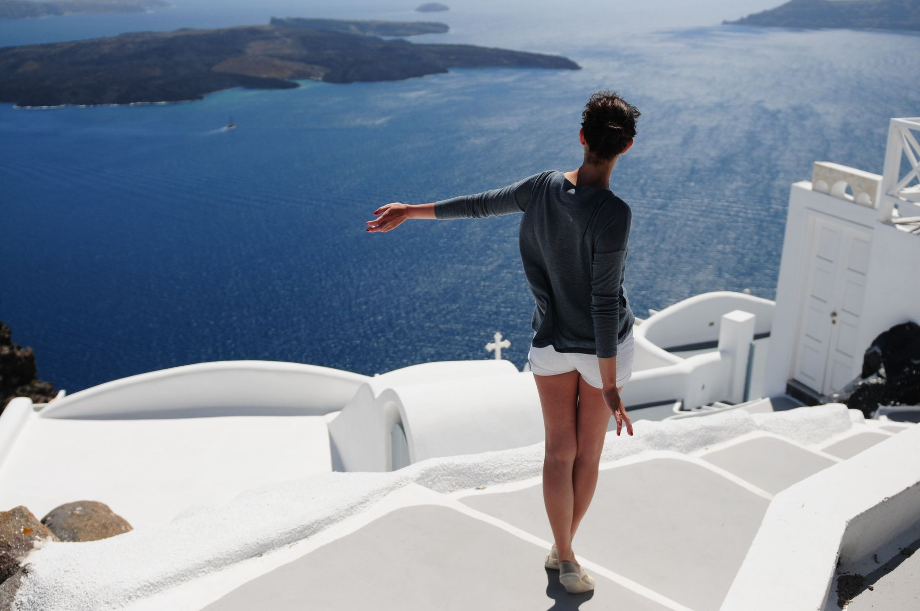 Solo traveler look out at the water in Greece, which is among the best places to travel alone