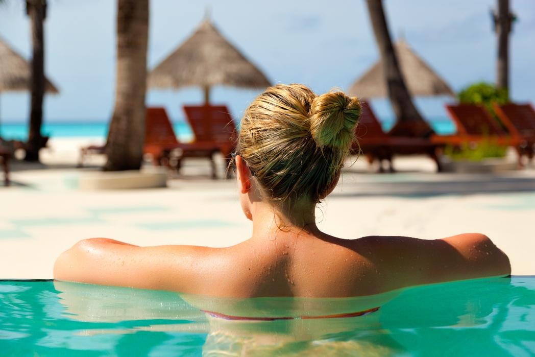 Γυναίκα απολαμβάνει τις διακοπές της χωρίς άγχος σε πισίνα ξενοδοχείου
