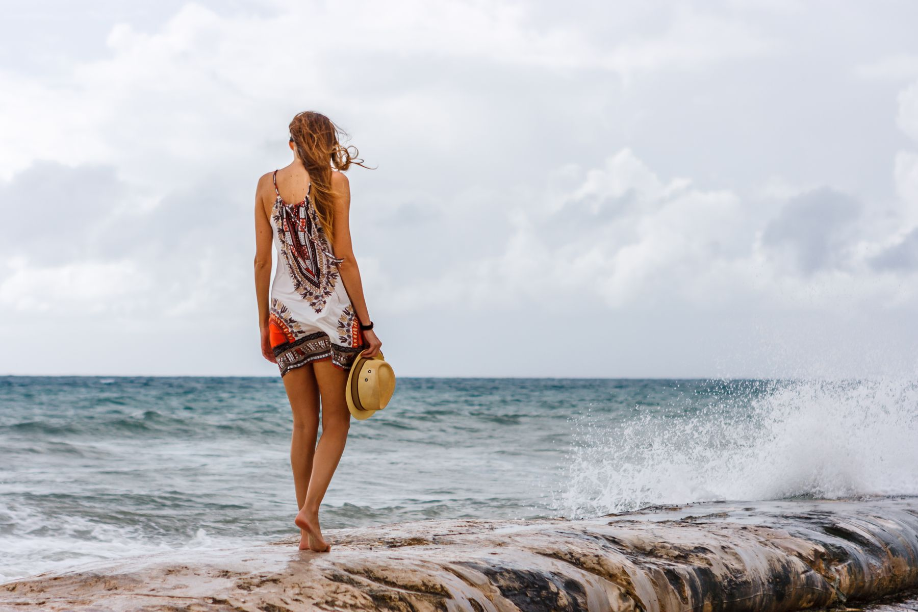 Woman with a hat in her hands staring at the sea at Playa del Carmen beach. Mexico is one of the best places to visit in May.
