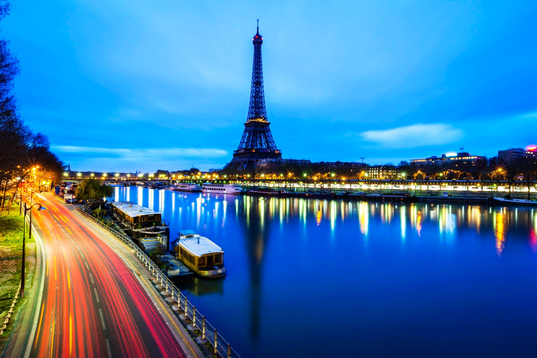 Long exposure shot of busy Parisian street and Eiffel Tower in blue hour