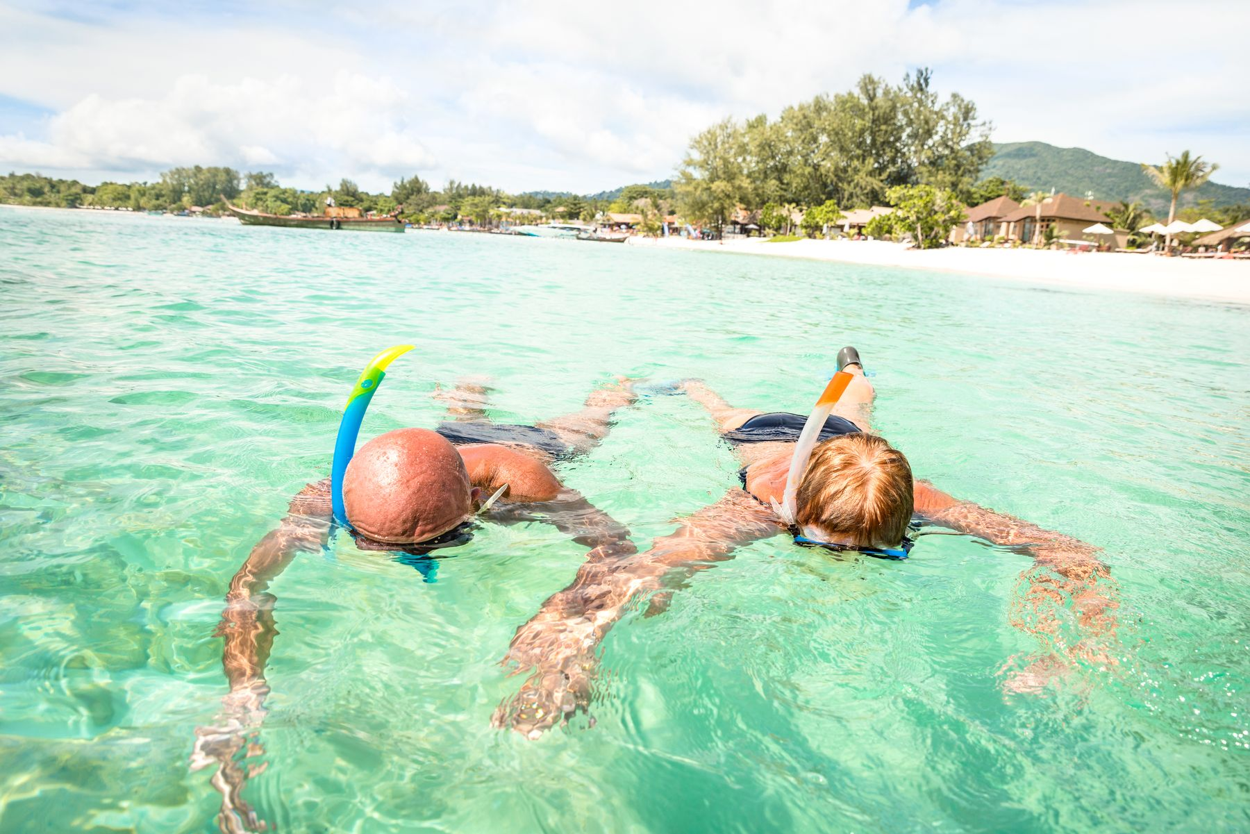 Senior couple vacationer swimming together on tropical Koh Lipe sea in Thailand