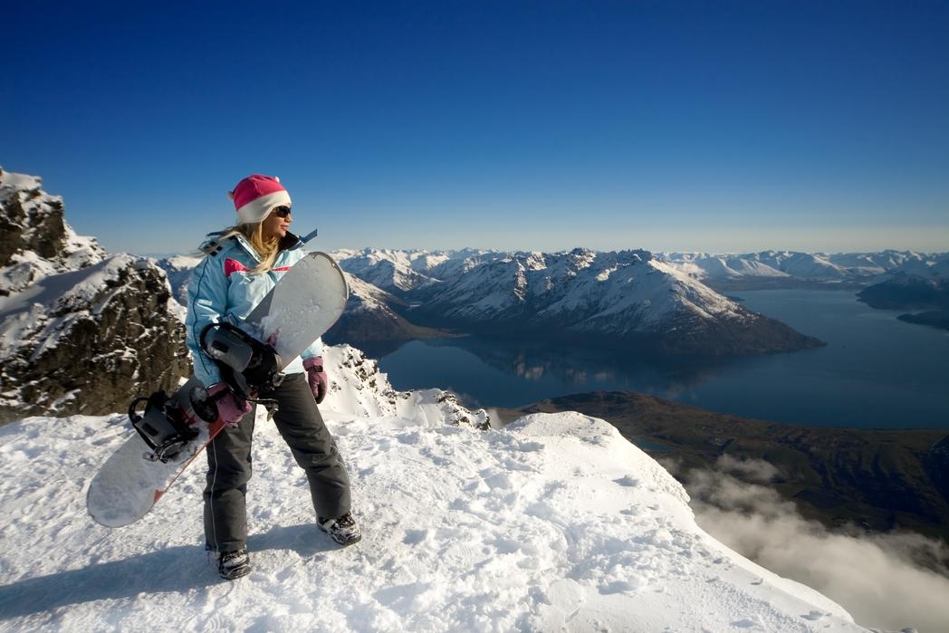 Snowboarder κοιτάει από ψηλά το βουνό.