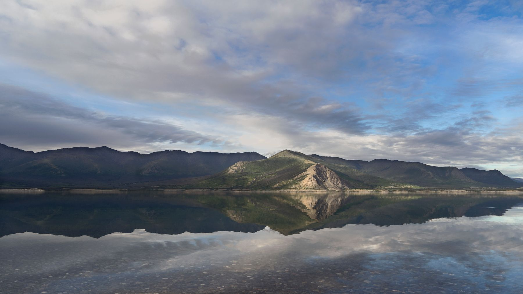 A mountain range reflected on a large body of water during daytime at Kluane national park in Canada.