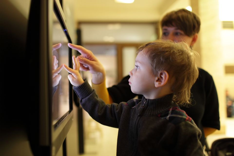 Two young boys tapping on a screen in a museum