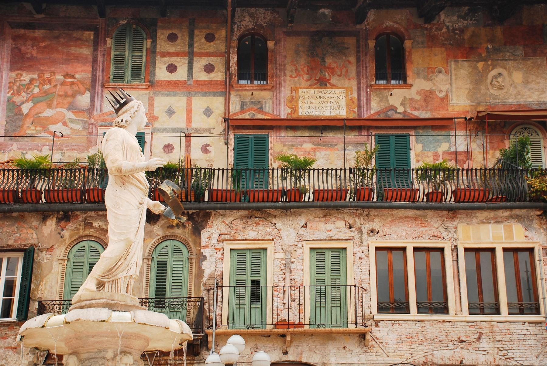 Фонтан Веронской Мадонны на фоне Дома Маццанти на Пьяцца делле Эрбе в Вероне.