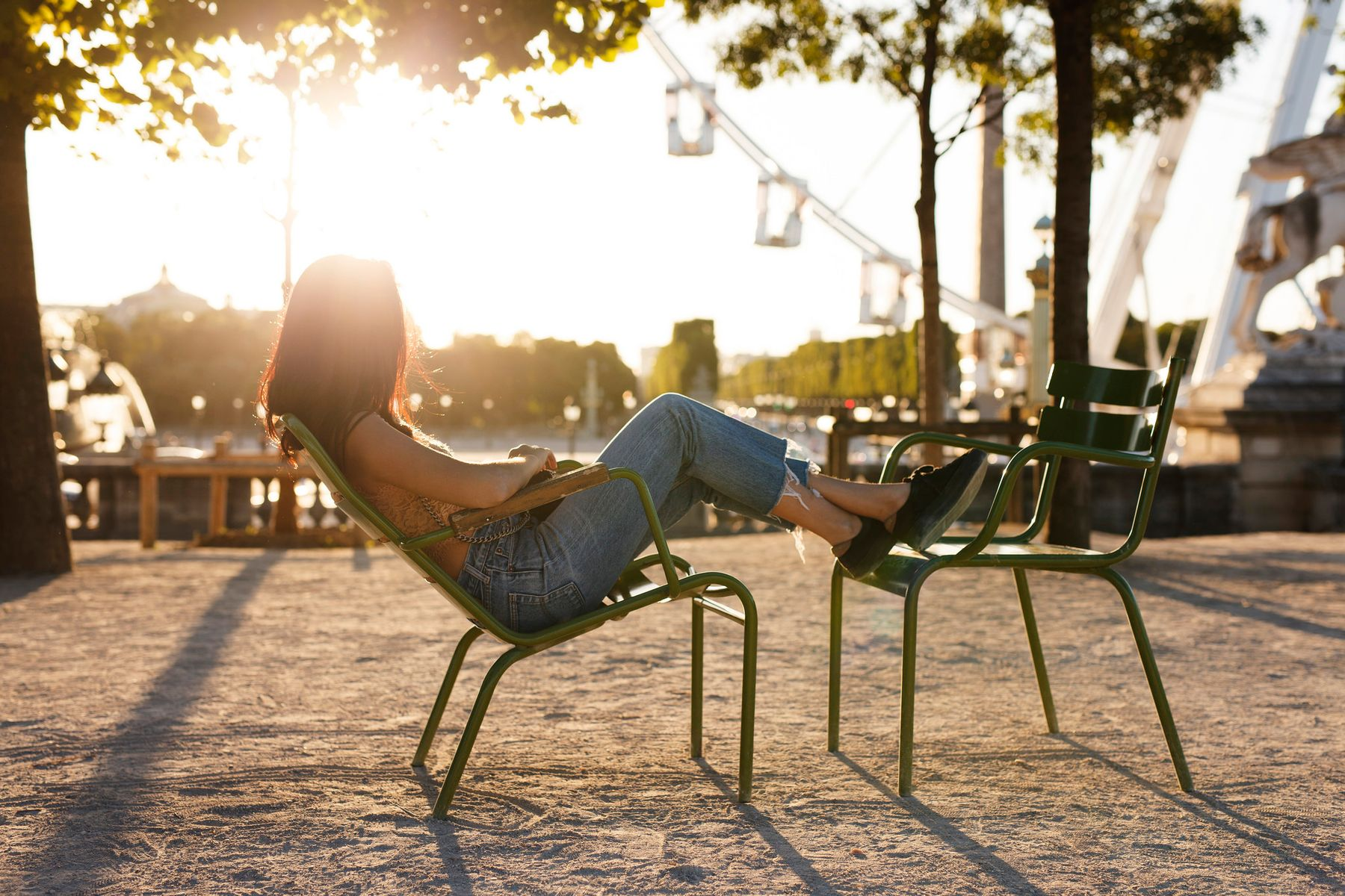 Young woman leaning back in a chair with her feet on another chair, watching a ferris wheel as the sun sets.
