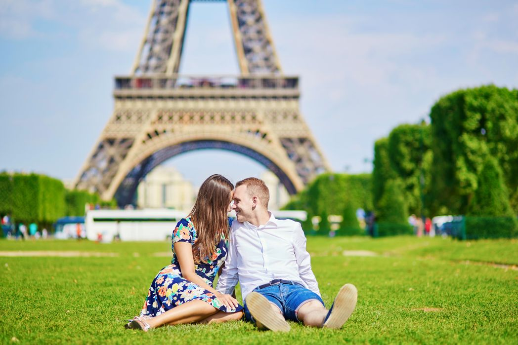 Couple on the grass in front of the Eiffel Tower in Paris
