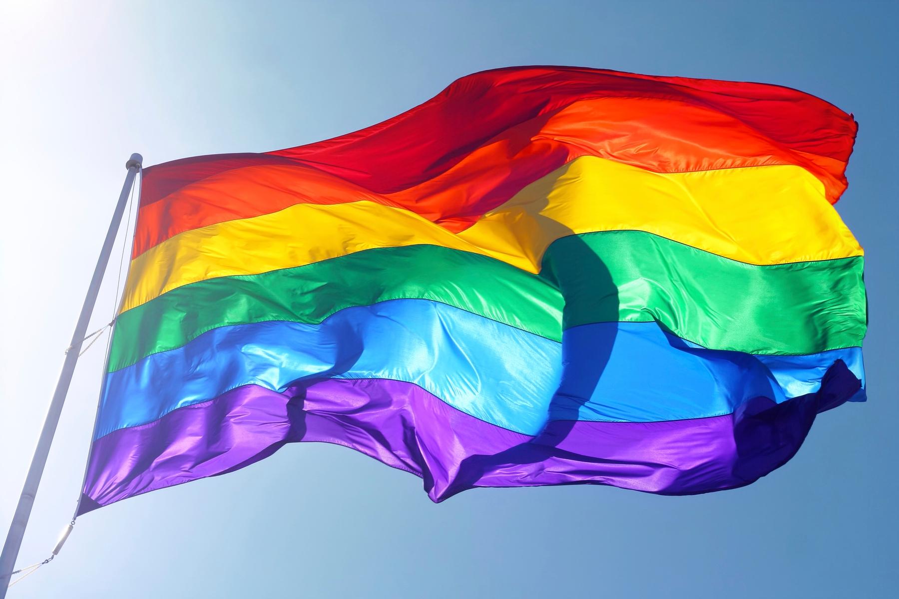 Rainbow-coloured Pride flag flying against a blue sky