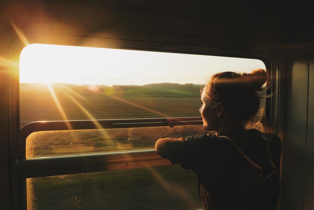 Κοπέλα απολαμβάνει το ηλιοβασίλεμα σ' ένα ταξίδι με τρένο