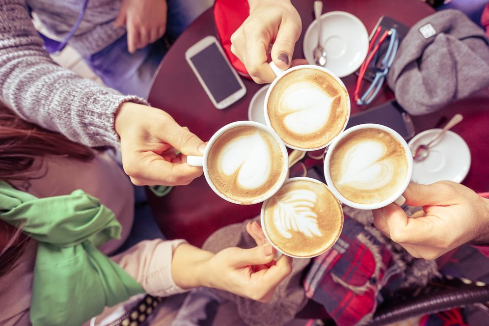 Friends raising their coffee cups at breakfast