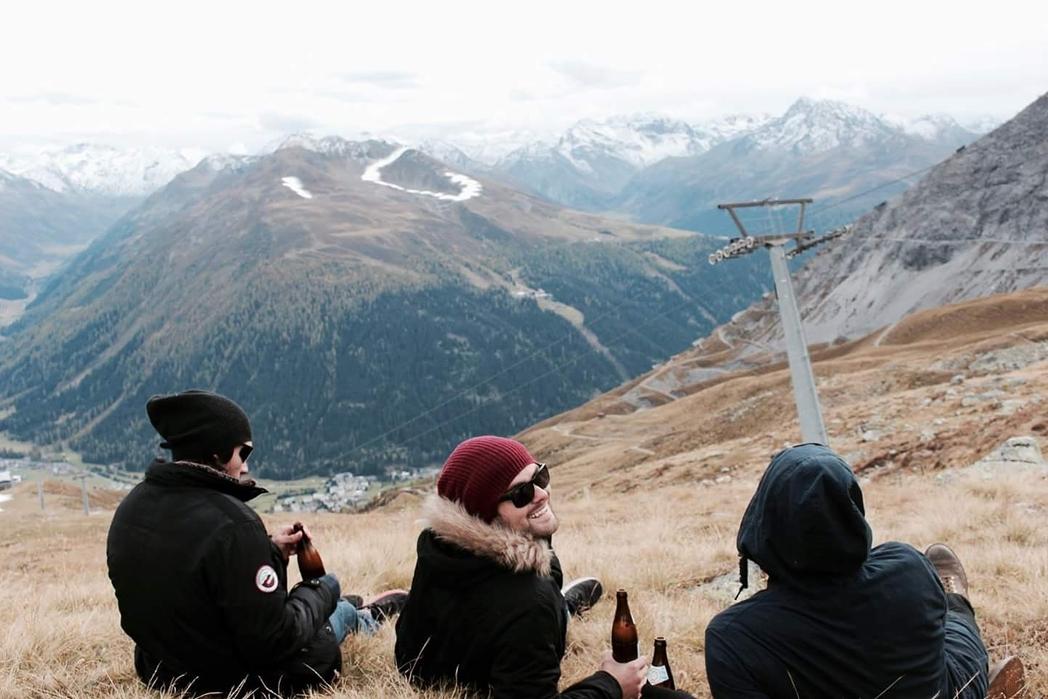 Τρεις φίλοι πίνουν μπίρες με θέα τις χιονισμένες κορυφές - οι καλύτεροι χειμωνιάτικοι προορισμοί στο εξωτερικό