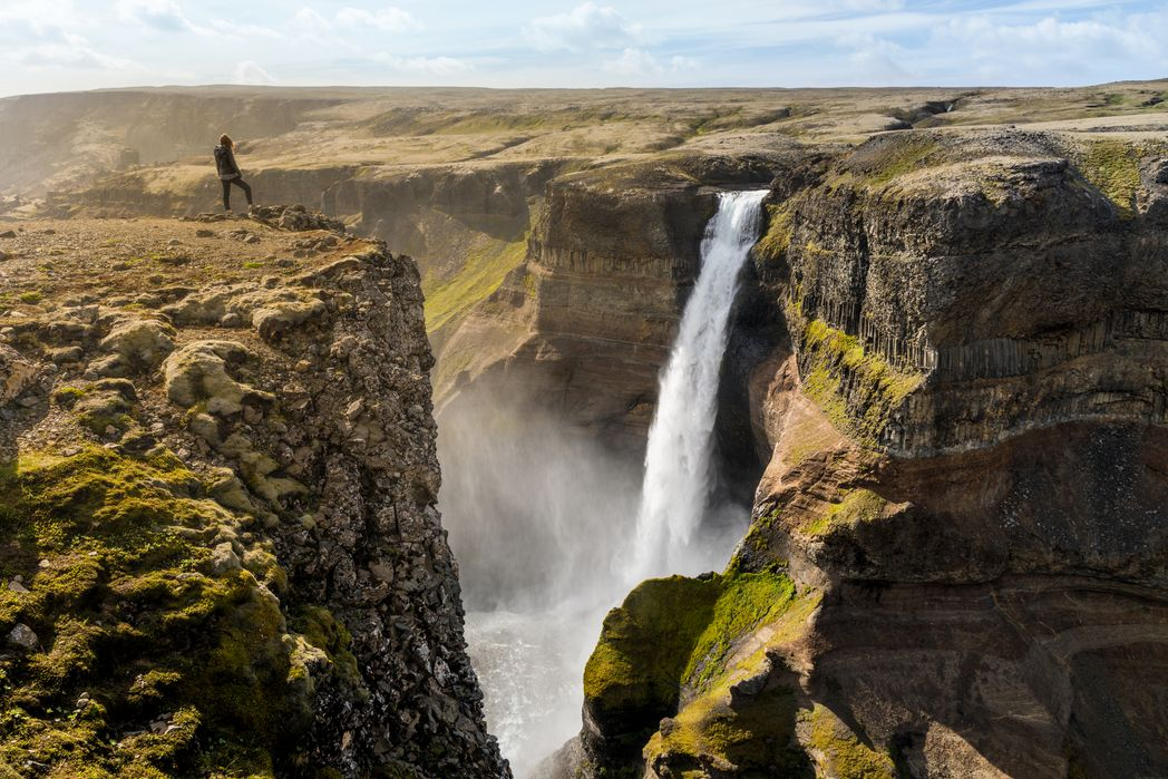 Traveller on top of a cliff watches a waterfall - best time to visit Iceland