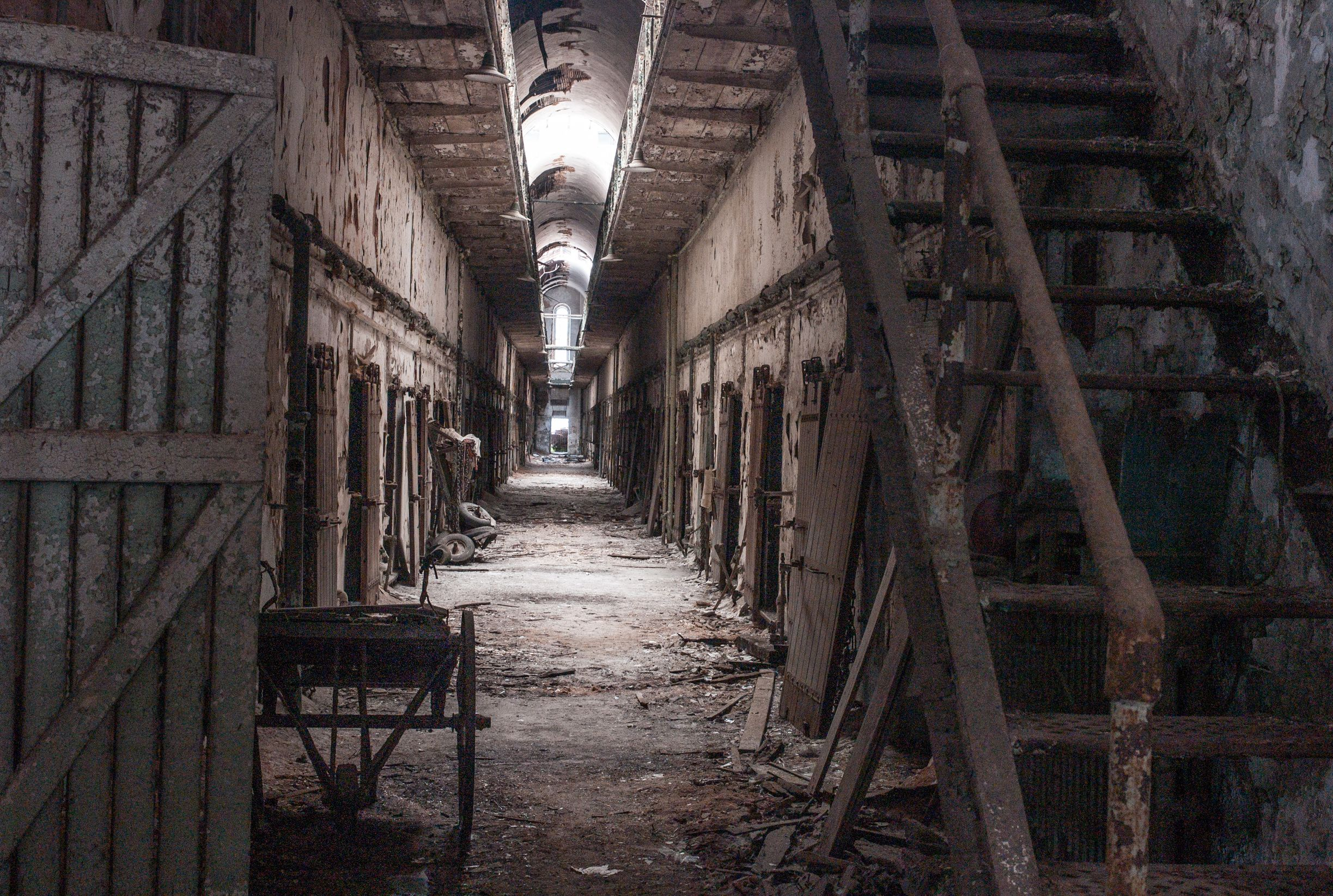 The crumbling interior of the Eastern State Penitentiary in Philadelphia, showing some metal steps going up and a row of doors lining a long and creepy corridor.