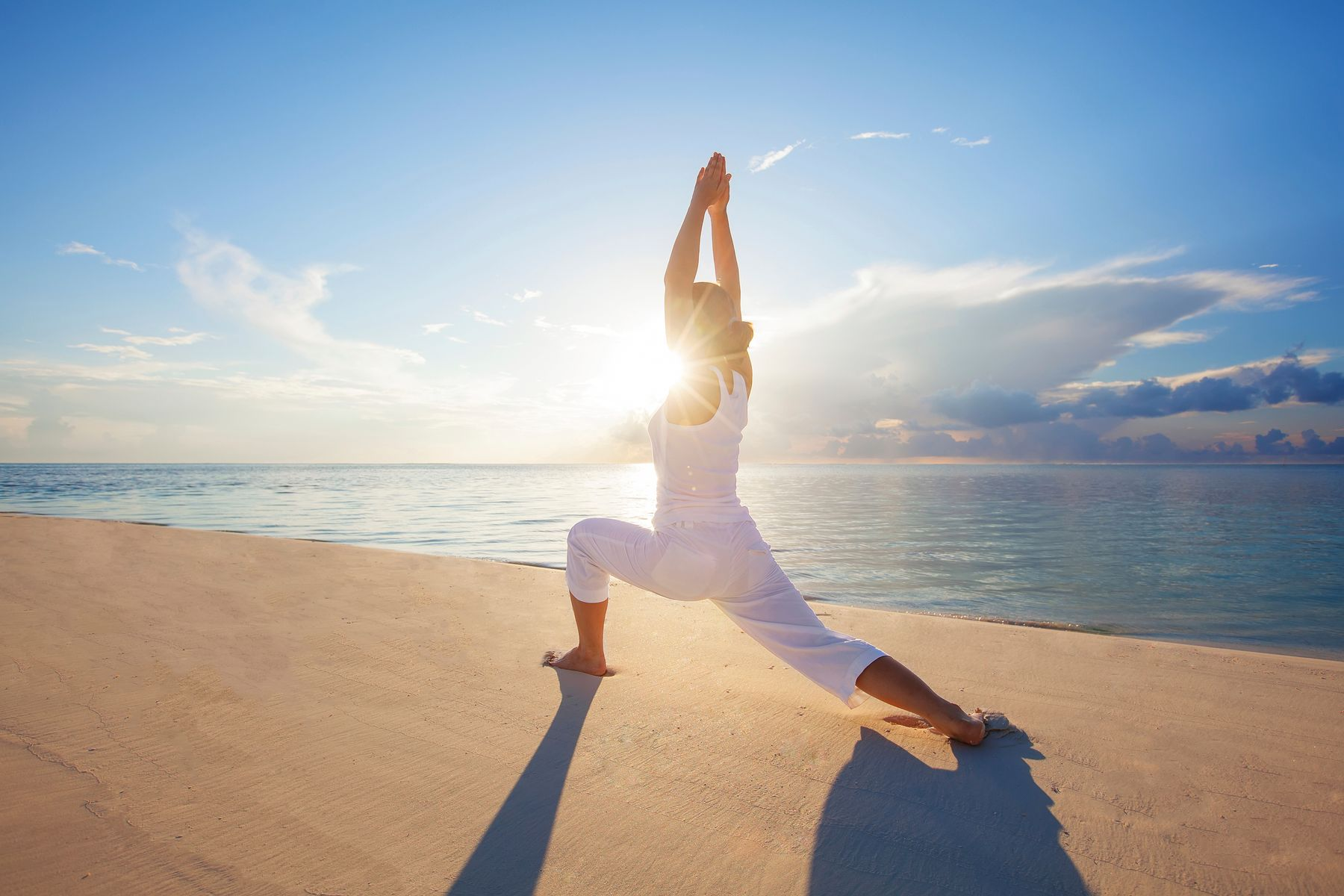 Woman doing yoga on the beach with the bright sun in the background